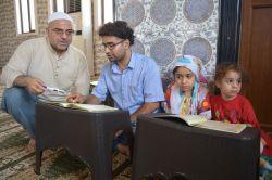 Baba çocuklarıyla Kur'an öğreniyor