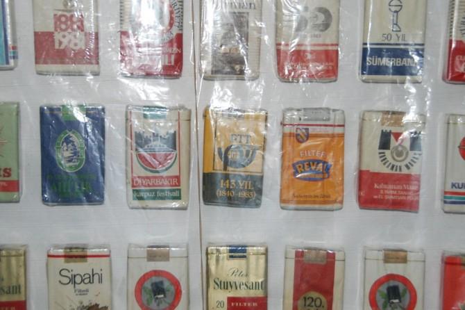 Bir zamanlar reklam için kullanılan sigara paketlerini sergiliyor