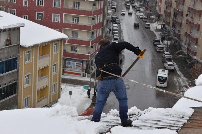 Ekmeğini çatıdan temizledikleri kardan çıkarıyorlar