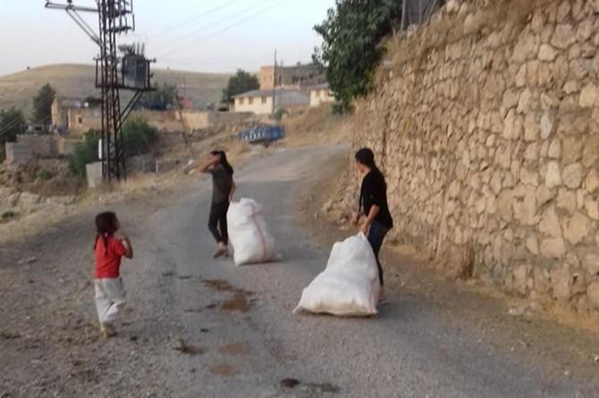 Çocuklarda çevre temizliği bilincini geliştirmek için onlarla birlikte çöp topluyor