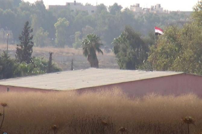 The Syrian regime troops hoist regime flag on public institutions in Qamişlo
