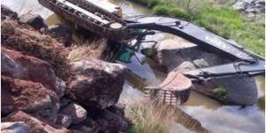 Viranşehir'de yol kenarında çalışma yapan kepçe 15 metre uçurumdan dereye düştü